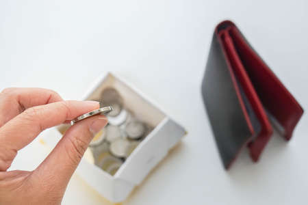 saving your money concept - woman put coin from wallet in a box for economical lives Stock Photo