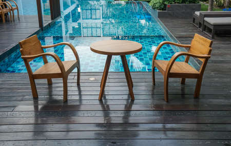 wooden table and chairs at the poolside for breakfast in luxury hotel
