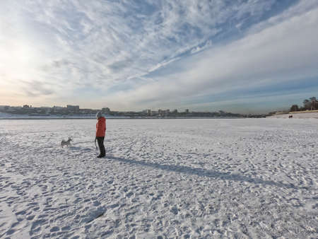woman walk the dog on frozen lake with thick snow in winter