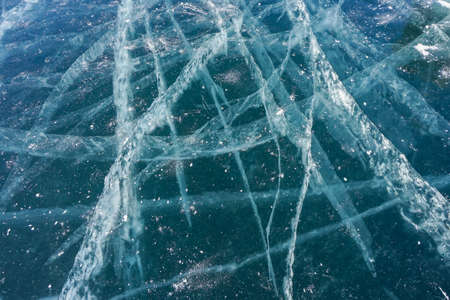 cracks on clear thick frozen Baikal lake in winter season with sunny blue sky Stock Photo