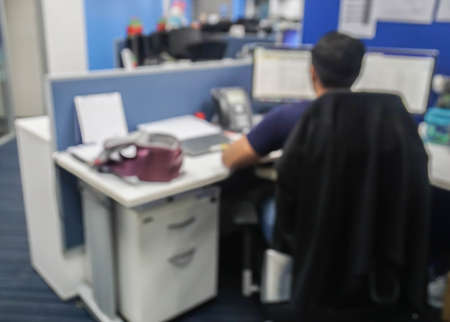 blur and defocus of workplace situation male office using computer in working hours