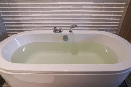 hot water in white ceramic bathtub in hotel bedroom