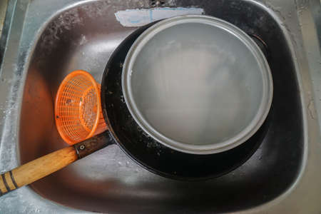 selective focus dirty pan in kitchen sink for cleaning after cooking Stock Photo