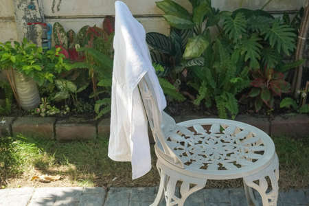 dry wet white towel on white outdoor chair