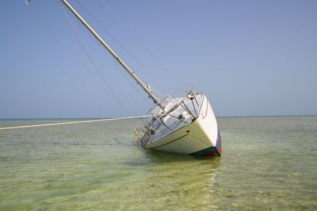 grounded: Weathered grounded sailboat on its side Stock Photo