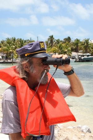 devised: Old captaing looking with binoculars out to sea Stock Photo