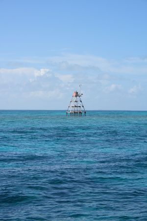 safe water: Navigational reef marker on the blue ocean Stock Photo