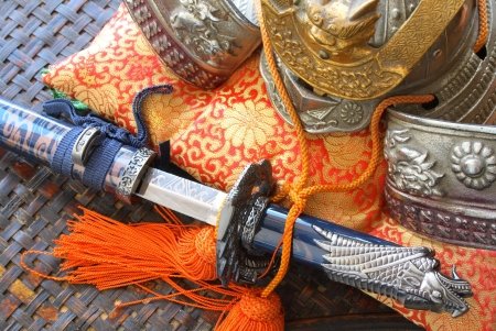 Samurai style helmet and sword with open blade on top of colorful silk cushion photo