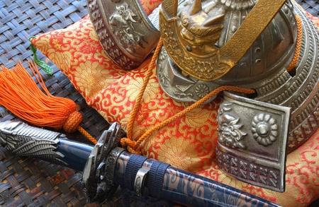 Samurai weapon and helmet on a silk colorful cushion photo