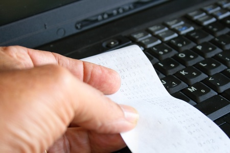 account executive: Hand holding a calculator printout with finances and laptop computer