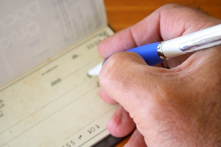 Male hand with pen filling a bank check photo