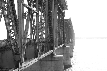 fading: Old steel railroad bridge over the ocean fading into the sun light monochrome