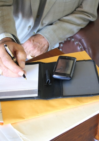 Businessman writing on notebook with cellular over legal folders photo