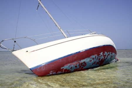 grounded: Grounded sailboat in the shallows of the ocean s coast