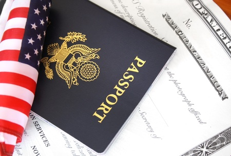 naturalization: Immigration concept, US passport and flag over a citizenship and naturalization certificate