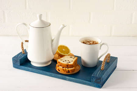 Slices of pound cake with raisins and a cup of coffee served on a tray. Morning tasty breakfast.