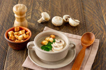 Mushroom cream soup with champignons, croutons and fresh herbs on rustic white wooden table.