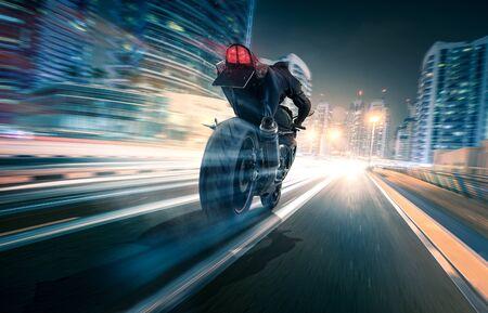 Motorcycle rides through a city at night Stock Photo