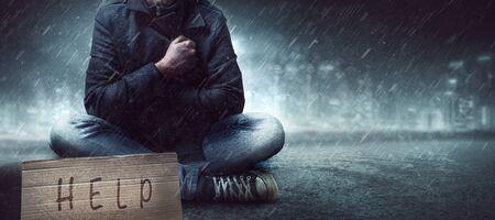 Homeless man on street in the rain