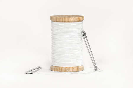 Spool of white thread and two safety pins isolated on white - 3d render