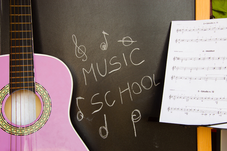Music school for children with purple guitar closeup on blackboard background and music sheets