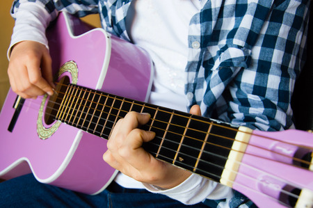 child: Music school for children with purple guitar closeup and child playing