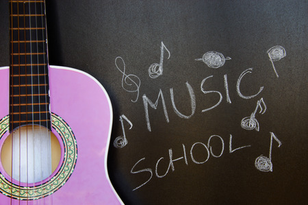 Music school for children with purple guitar closeup on blackboard background Stock Photo