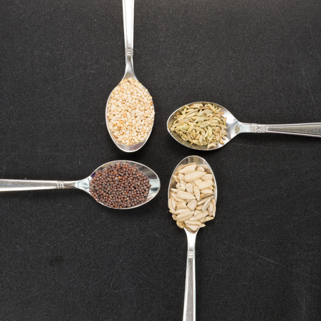 macrobiotic: Spoon of sunflower sesame fennel mustard seeds for macrobiotic food on background background