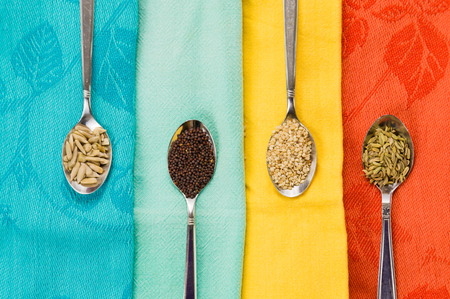 macrobiotic: Spoon of sunflower sesame fennel mustard seeds for macrobiotic food on colorful background