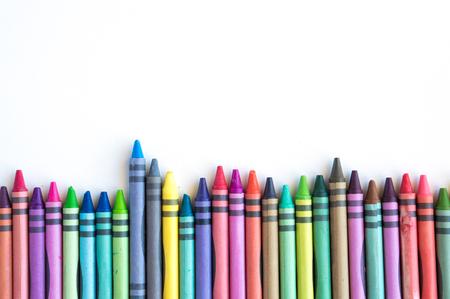 Kleurpotloden en pastels opgesteld in de regenboog op een witte achtergrond.
