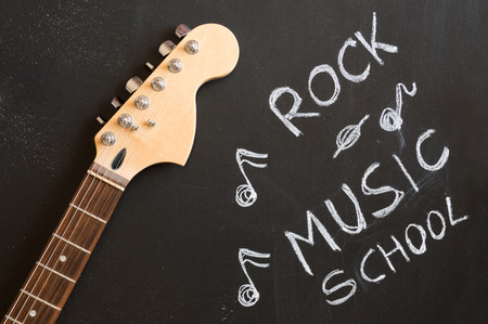 Rock music school with electric guitar on blackboard background