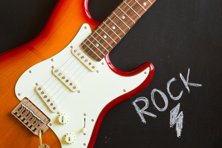 Red electric guitar rock closeup on blackboard background