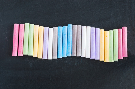 lined up: Colorful chalks lined up on school blackboard background