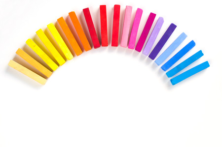 lined up: Rainbow of colorful chalks lined up rounded on circle on white background Stock Photo