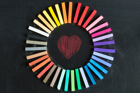 lined up: Colorful chalks lined up rounded on circle on blackboard background with heart for love and passion
