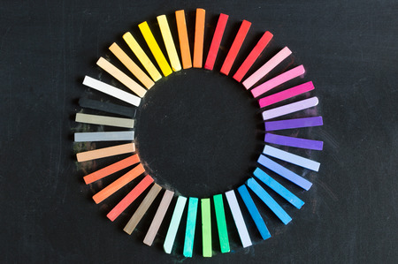 lined up: Colorful chalks lined up rounded on circle on blackboard background
