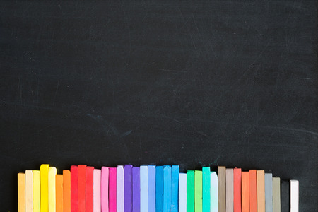 lined up: Colorful chalks lined up on blackboard background banner