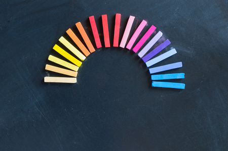 lined up: Rainbow of colorful chalks lined up rounded on circle on blackboard background