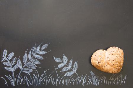wholegrain mustard: Heart shape of wholemeal bread on blackboard background