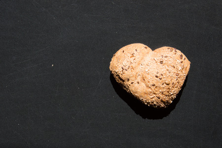wholegrain mustard: Heart shape of wholemeal bread with sunflower seeds on blackboard background