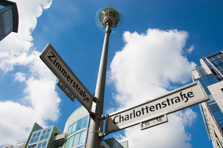 Street sign pointing to Zimmerstrasse and Charlottenstrasse with buildings and sky clouds at background