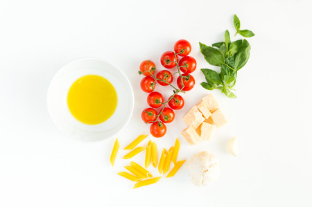 close up food: Italian red tomatoes close up food with pasta, basil leafs, cheese, isolated on white background - Flat lay Stock Photo