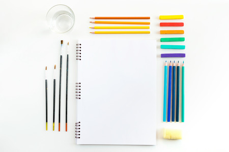 Sketchbook mock up for artwork with watercolor paints, pastels, glass of water and a paintbrushes. Top view. Artistic work tools on white wooden table. Stock Photo
