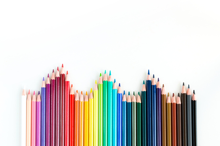 lined up: Crayons and watercolor pastels lined up isolated on white background Stock Photo
