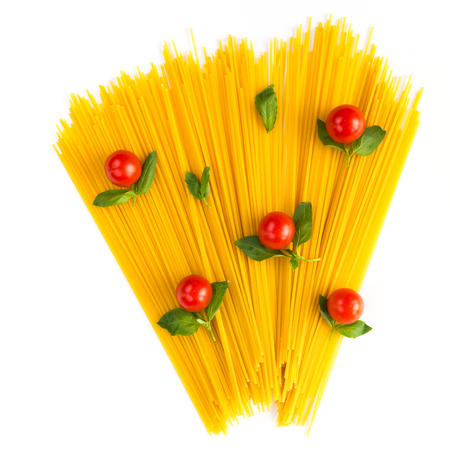 Italian spaghetti raw ingredients with red tomatoes and fresh basil leafs on a white board background, top view