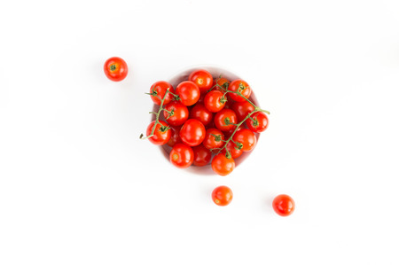 Dish of Italian raw red tomatoes cherry closeup isolated on white background