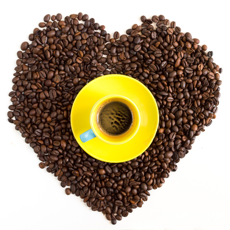 Heart of coffee beans with yellow cup isolated on white background