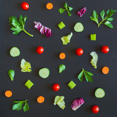 Eating pattern raw with ingredients of salad, lettuce leaves, cucumbers, red tomatoes, carrots, celery on blackboard background