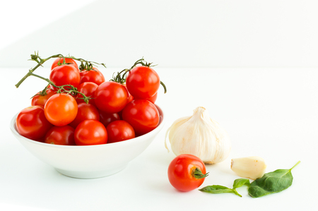 Italian red tomatoes close up food with garlic, basil leafs, isolated on white background