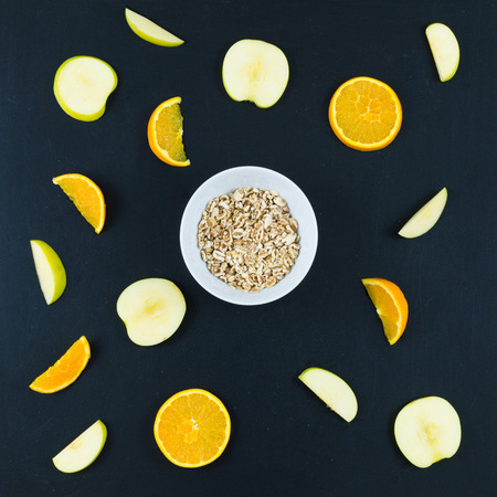 Good morning with healthy breakfast with composition flat lay of sliced apple and orange, oats and whole spelled isolated on blackboard background - top view Stock Photo - 103246622